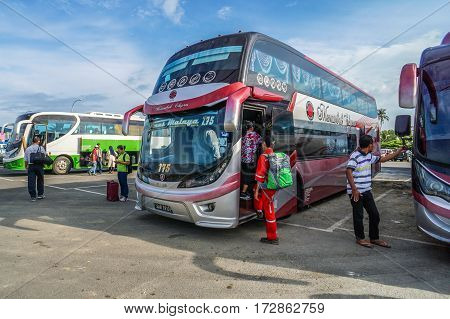 Menumbok,Sabah-Aug 19,2016:People walking up to the bus in bus terminal at Menumbok,Sabah.People used to take bus from Kota Kinabalu to Menumbok then ferry to Labuan island to enjoy tax free shopping