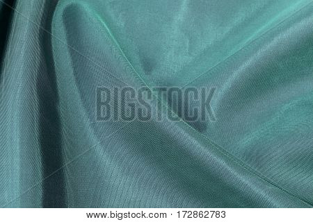Silk background texture of green shiny fabric close up