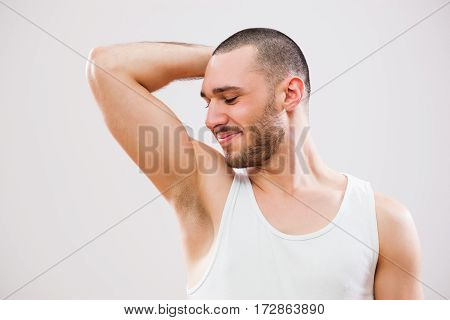 Young man is smelling his armpit after shower.