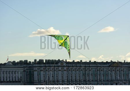 green kite floating in the blue sky over the Neva river and the Hermitage Museum St. Petersburg Sunny day