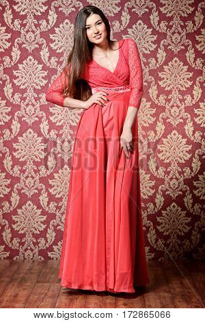 Full length portrait of a beautiful young woman wearing evening red dress posing over vintage wallpaper. Beauty, fashion.