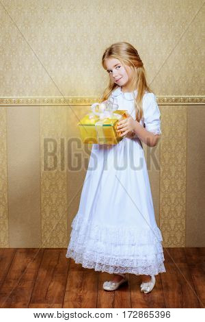 Holiday concept - Christmas, birthday. Beautiful little girl in white dress holding a gift box. Kid's fashion.