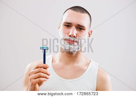Young man is bored because he has to shave his beard.