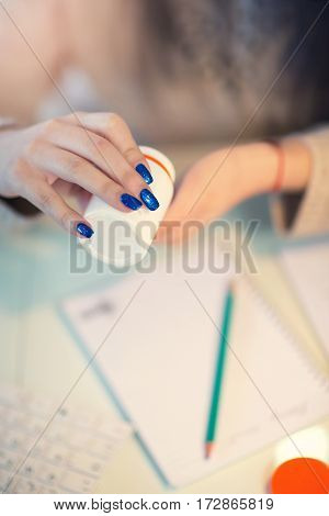 Woman hand holding pills sick and working business on office desk