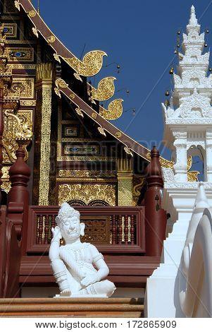 White Lanna style Thai sleeping guardian statue in front of Hor Kham Luang in The Royal Flora Ratchaphruek Garden Chiang Mai Thailand