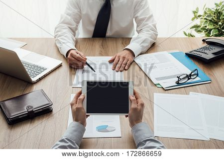 Business partners working at office desk they are analyzing financial reports and using a digital tablet point of view shot