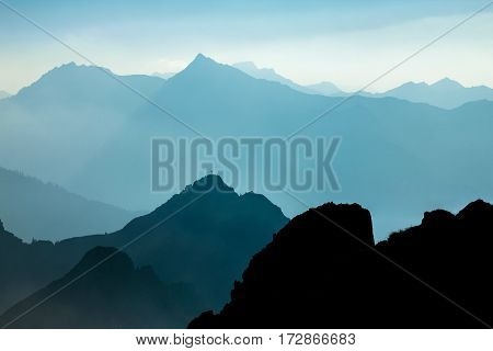 Blue and cyan mountain ranges silhouette with bright back light. Tirol, Austria. Summit cross is visible on the first mountain peak.