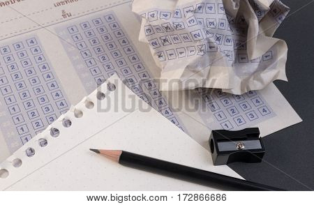 Crumpled paper ball of vintage classic answer sheet with pencil sharpener and paper reduction. Cross the right answer in the box with blank answer. Answer sheet concept.