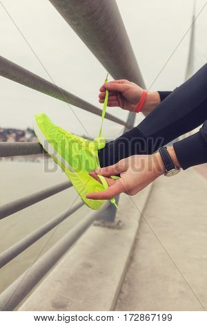 Urban jogger tying running shoes on the sidewalk of a bridge.