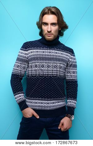 Handsome young man wearing sweater over blue background. Winter fashion. Hairstyle. Studio shot.