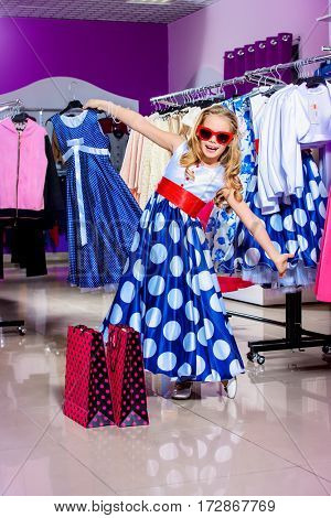 Little fashion-monger girl wearing beautiful pin-up dress and sunglasses goes shopping. Children's fashion. Sale and shopping concept.