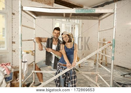 Happy young couple renewing home, smiling under scaffold.
