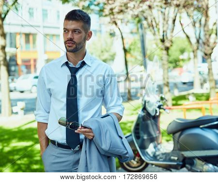 Portrait of businessman on street in urban setting. Young elegant handsome man.