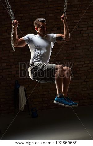 Muscular man doing crossfit workout with chain, indoors.