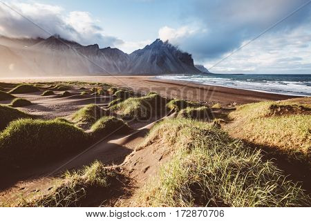 Unusual hills glowing by sunlight. Dramatic and gorgeous scene. Tourist attraction. Location Stokksnes cape, Vestrahorn (Mt. Batman), Iceland, Europe. Vintage effect. Instagram filter. Beauty world.