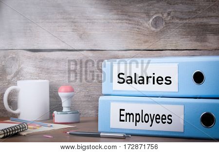Employees and Salaries. Two binders on desk in the office. Business background.