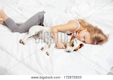 Child sleeping with dog. Girl with pet at home