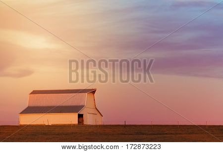 Barn in the midwest with the golden light from the sunset shining on it.