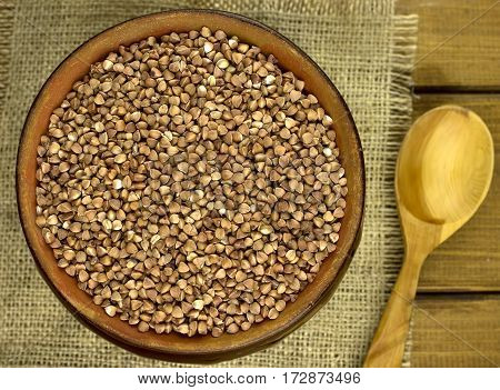 Buckwheat groats in a bowl and wooden scoop with buckwheat
