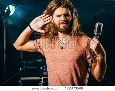 Photo of a rock and roll singer on stage listening to the concert crowd reactions.