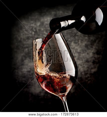 Red wine pouring in wineglass on a black background.