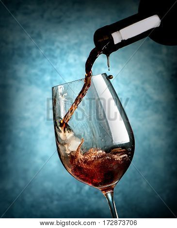 Red wine pouring in wineglass on a blue background.