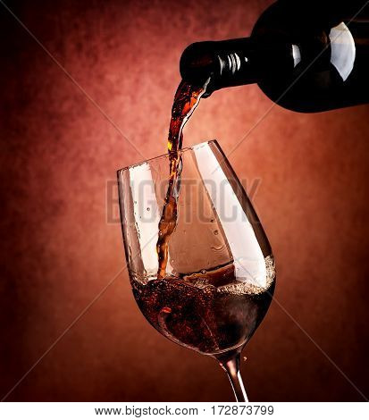 Red wine pouring in wineglass on a brown background.