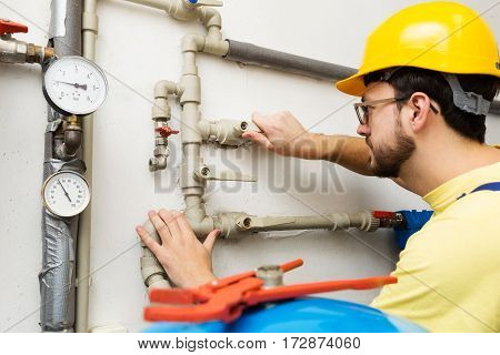 plumber doing maintenance jobs for water and heating systems