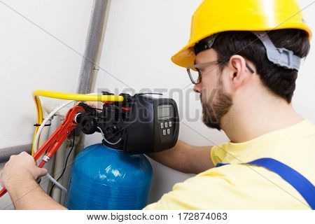 plumber with wrench installing new water filtration system