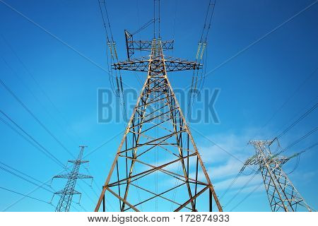 Electricity Pylon and Power Lines on Blue Sky Background