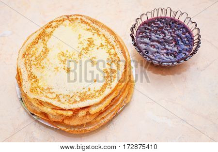 Pancakes with raspberry jam on the table. Maslenitsa Festival