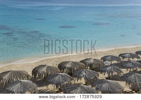 Top view of sand beach with sunshades. Sunshades are made from palm leaves.