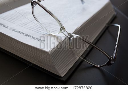 Glasses on the Open Book. Close-Up of Glasses.