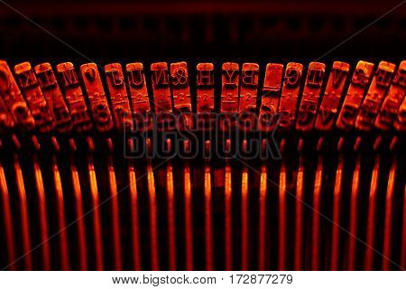 Closeup of old typewriter plates strikers with letters and symbols for typing.