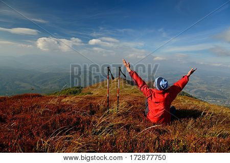 Tourist with outstretched hands sitting on alpine meadow. Sky and mountain ranges in background. Red bilberry leaves in foreground.