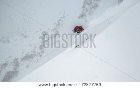 Freeride under snow fall. Skier dressed in red cloth.