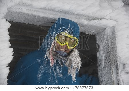 Girl with ski goggles covered with frost. Frosted door is frame of portrait.