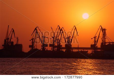 Harbor at sunset. Cranes silhouettes against orange sky.
