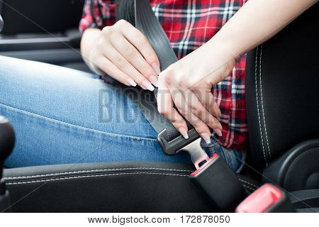Close up of female hands fastening seat belt in car. Safety driving concept