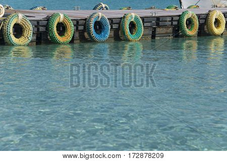 Pier with multicolored tires defending ships during stop. Blue transparent sea in foreground.