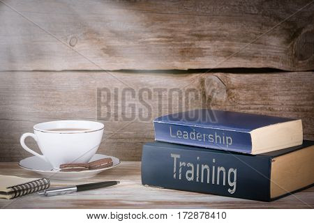 Training and Leadership. Stack of books on wooden desk.