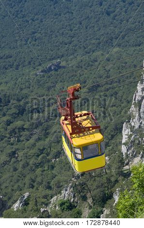 Bright yellow cable railway carriage hangs over the precipice. Place - Crimea. Route Alupka - Ai-Petri.