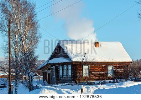 Rustic log house among the snowdrifts. Russian old-believer village Visim in the low Middle Ural Mountains of Sverdlovsk region, Russia
