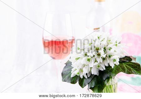 Snowdrop bouquet, white spring flowers and pink wine on light background. Copy space, horizontal