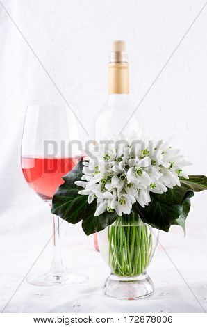 Snowdrop bouquet, white spring flowers and pink wine on light background, vertical