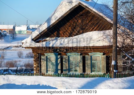 Snow-covered old log house with wooden shutters. Russian old-believer village Visim in the low Middle Ural Mountains of Sverdlovsk region Russia