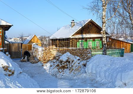 Snow-covered wooden houses and heaps of firewood in a russian old believer village Visim. Ural region, Russia.