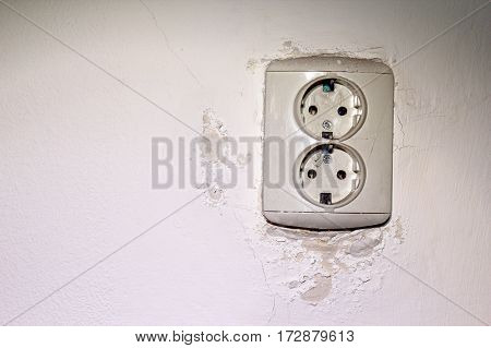 old electrical socket mounted on wall damaged by water leakage