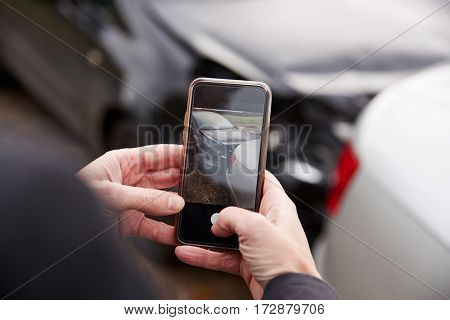 Woman Taking Photo Of Car Accident On Mobile Phone