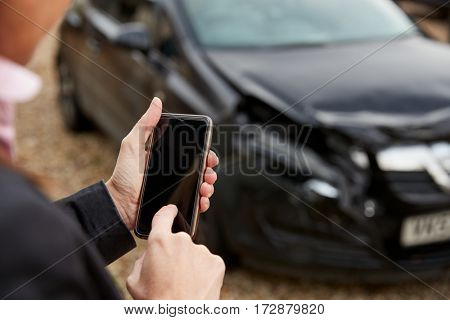 Loss Adjuster Taking Photo Of Damaged Car On Mobile Phone